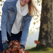 Woman collecting leaves — Stock Photo
