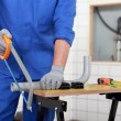 Plumber sawing plastic pipe — Stock Photo