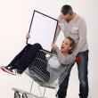 Couple with trolley holding picture frame — Stock Photo #11486504