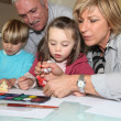 Foto Stock: Grandparents painting with their grandchildren