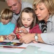 Grandparents painting with their grandchildren - Stock Photo