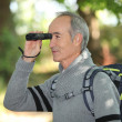 Stock Photo: Senior backpacker looking through binoculars
