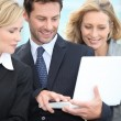 Three colleagues stood outside using laptop computer — Stock Photo