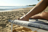 Woman relaxing on a sun lounger at the beach — Stock Photo