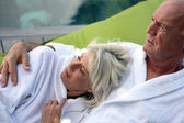 Middle-aged couple relaxing on decking — Stock Photo