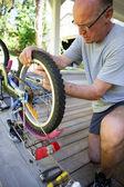 Man repairing a bike on his terrace — Stock Photo