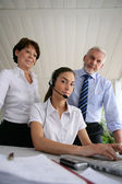 Business at a laptop with headset — Stock Photo