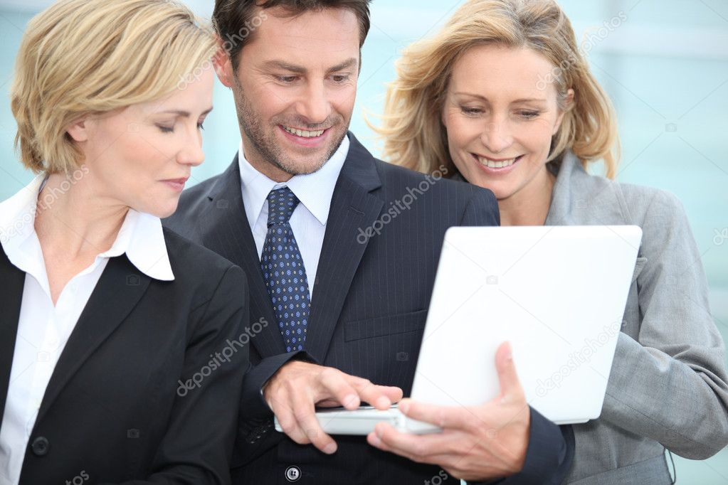 Three colleagues stood outside using laptop computer — Stock Photo #11489669
