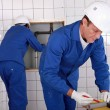 Plumbers working in a tiled room - Stockfoto
