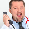 Moon-faced doctor with stethoscope arguing on phone — Stock Photo #11493762