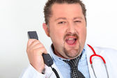 Moon-faced doctor with stethoscope arguing on phone — Stock Photo
