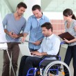 Man in wheelchair surrounded by colleagues - Stock Photo