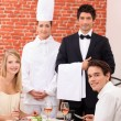 Restaurant staff stood with customers - Stock Photo