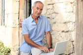 Man with computer front door — Stock Photo
