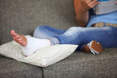 Woman with sprained ankle reading on the sofa — Stock Photo