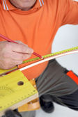 Laborer measuring copper tube — Stock Photo
