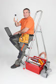 Plumber sitting on stepladder showing phone — Stock Photo