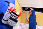 Two electrician working on ceiling electrics — Stock Photo