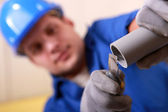 Plumber sanding the end of a pipe — Stock Photo