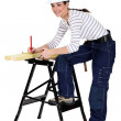 Stock Photo: Tradeswommarking measurement on wooden plank