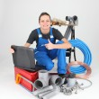 Female plumber with tools of the trade and a laptop computer — Stock Photo