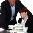 Architect and assistant looking at model house — Stock Photo
