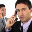 Stock Photo: Two businessmen on their mobile telephones