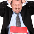 Businessman tearing his hair out over a pile of paperwork — Stock Photo #11637024