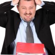Stock Photo: Businessmtearing his hair out over pile of paperwork