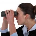 Woman watching through binoculars — Stock Photo #11637061