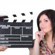 Stock Photo: A woman posing near a movie clap