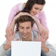 Couple laying on bed with laptop — Stock Photo