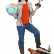 Cute brunette apprentice holding globe with foot resting on recycling tub — Stock Photo