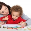 Stock Photo: Mother teaching her child how to draw
