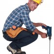 图库照片: Tradesmusing power tool with long bit