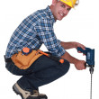 Stock Photo: Tradesmusing power tool with long bit