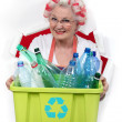 Granny with hair curlers holding recycling tub full of plastic bottles — Stock Photo #11637586