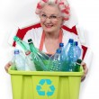 Granny with hair curlers holding recycling tub full of plastic bottles - Stock Photo