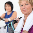 Mature women using gym equipment — Stock Photo