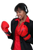 Businesswoman wearing a headset and boxing gloves — Stock Photo