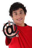 Young man with an @ sign — Stock Photo