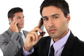 Two businessmen on their mobile telephones — Stock Photo