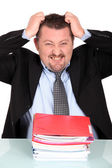 Businessman tearing his hair out over a pile of paperwork — Stock Photo