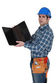 Tradesman looking at the underside of his laptop — Stock Photo