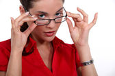 Woman putting on glasses — Stock Photo