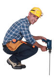 Tradesman using a power tool with a long bit — Stok fotoğraf
