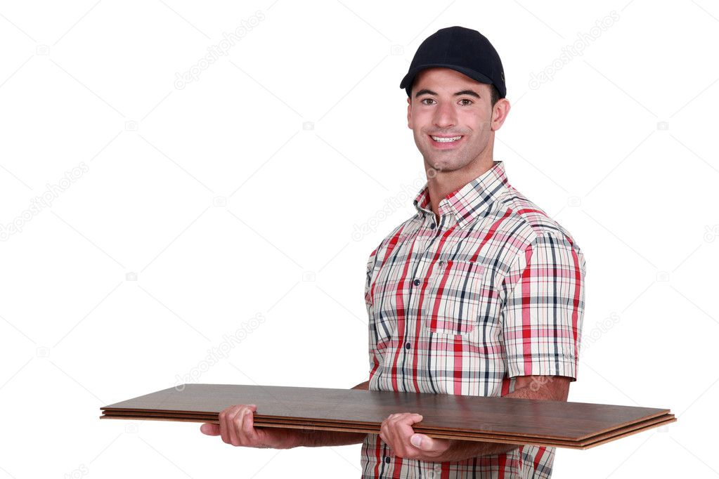 Craftsman holding a few floor boards — Stock Photo #11637573