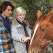 Stock Photo: Young couple taking care of horse