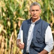 Stock Photo: Experienced farmer standing in his field