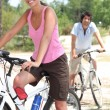 Foto Stock: Young couple riding bikes in the countryside